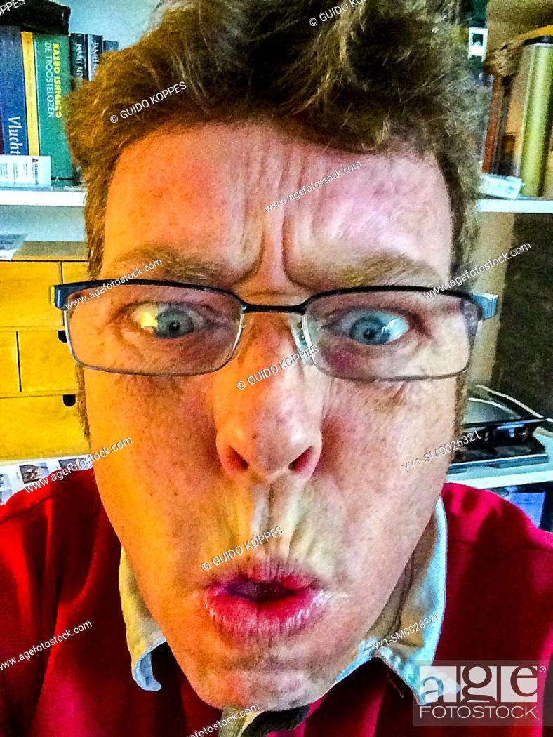 Imagen: Tilburg, Netherlands. Mature adult male making faces into his smartphone camera.