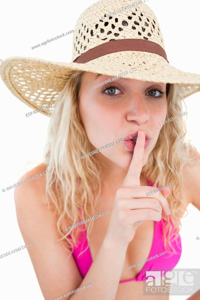 Stock Photo: Young woman telling to be quiet with her finger on her mouth.