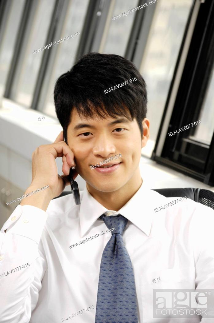Stock Photo: Businessman talking on a mobile phone in an office.