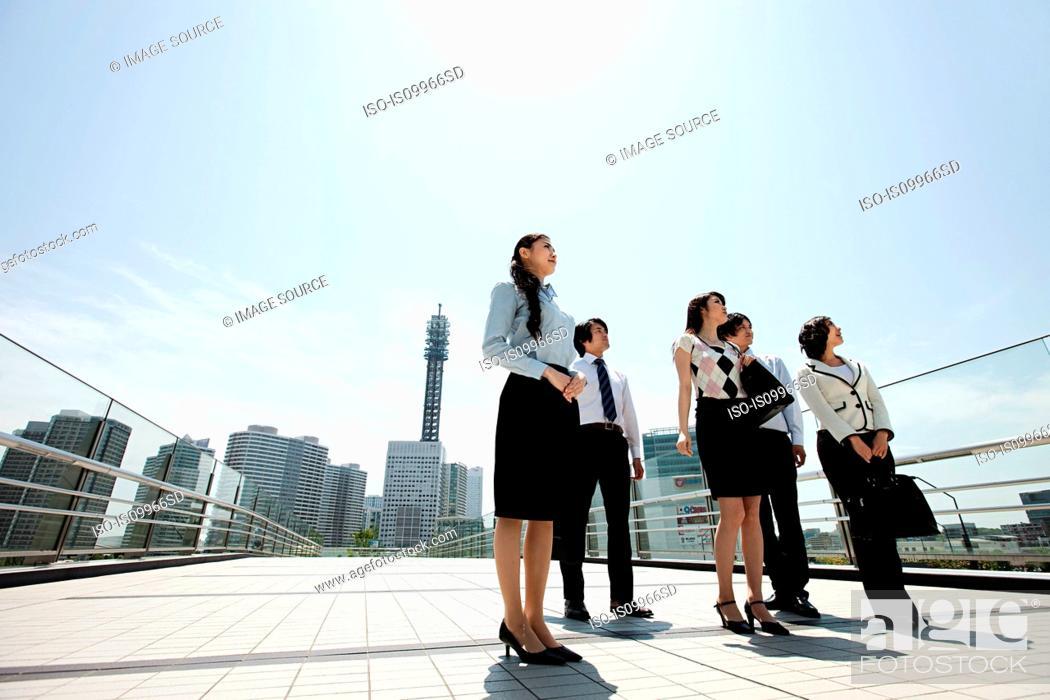 Stock Photo: Businesspeople in city scene.