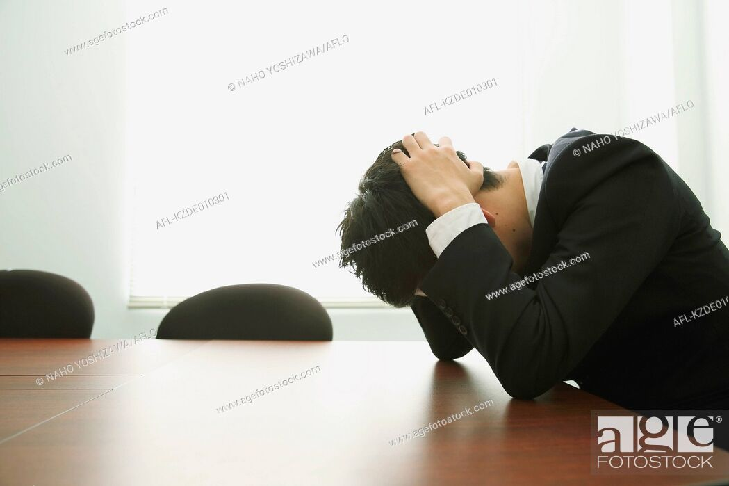 Stock Photo: Desperate Japanese young businessman in a suit.