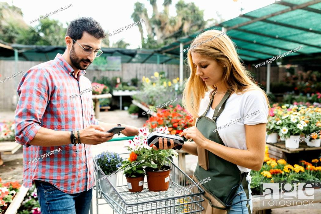Imagen: Customer paying with smartphone in a garden center.