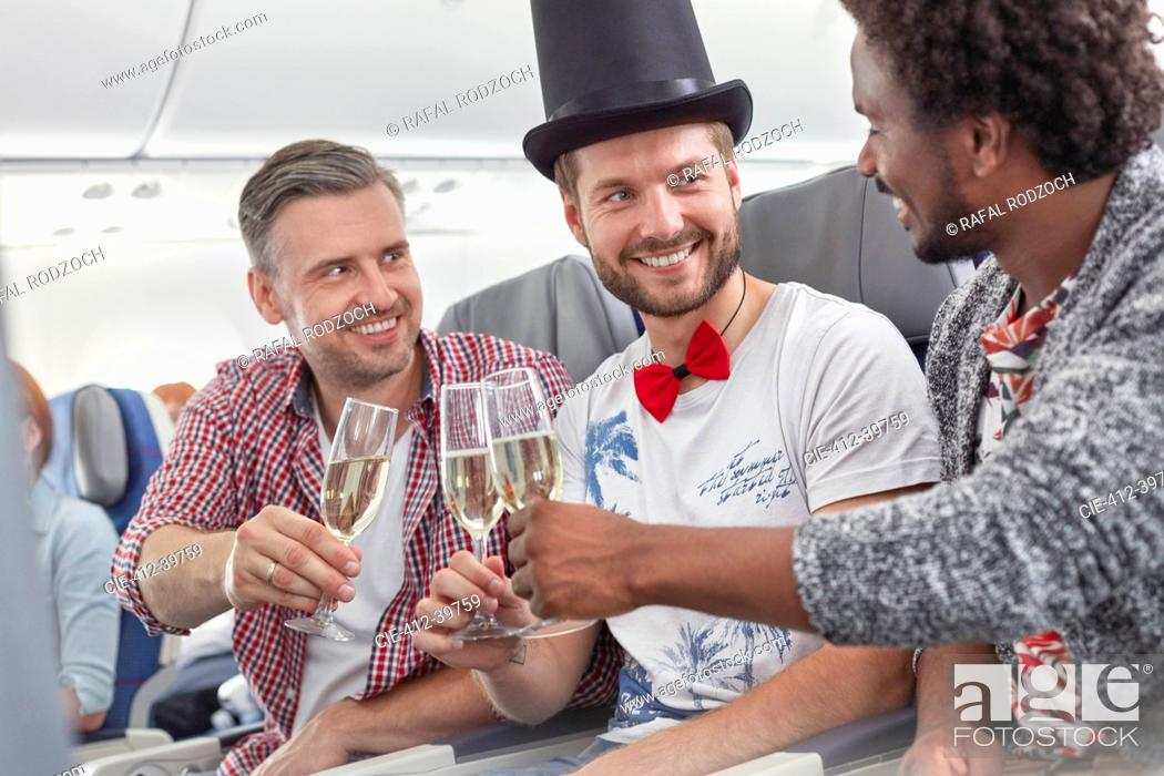 Stock Photo: Young male friends toasting champagne glasses on airplane.