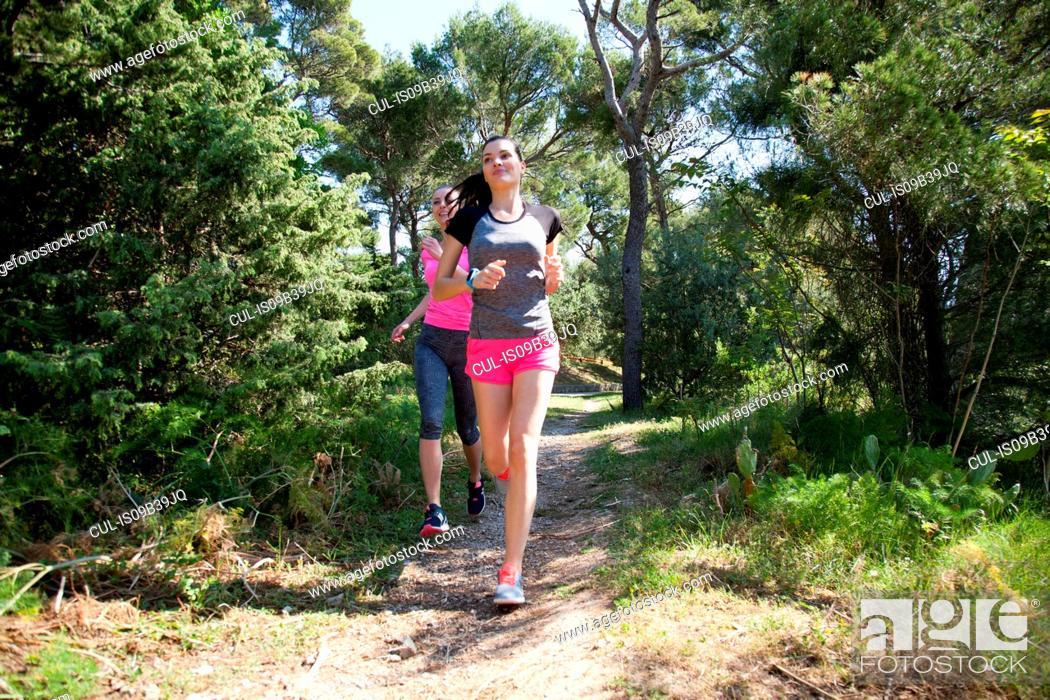 Stock Photo: Two female runners running in park, Split, Dalmatia, Croatia.