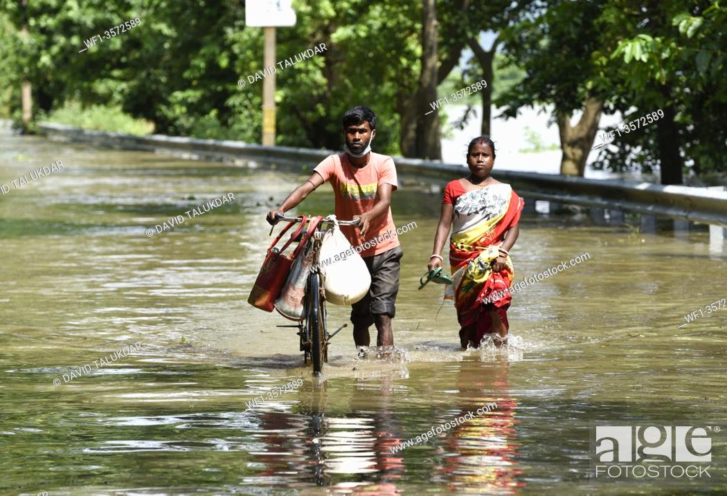 Stock Photo: Villagers waking wade through a flooded road, in Morigaon district of Assam, Monday, July 13, 2020.