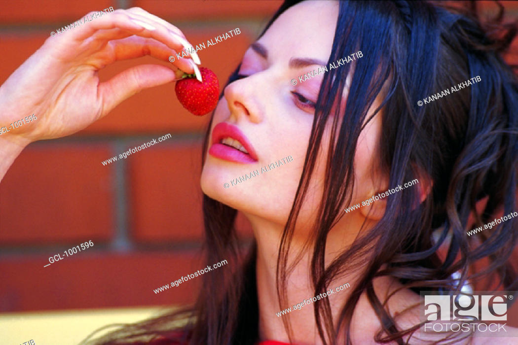 Stock Photo: Woman eating strawberry.