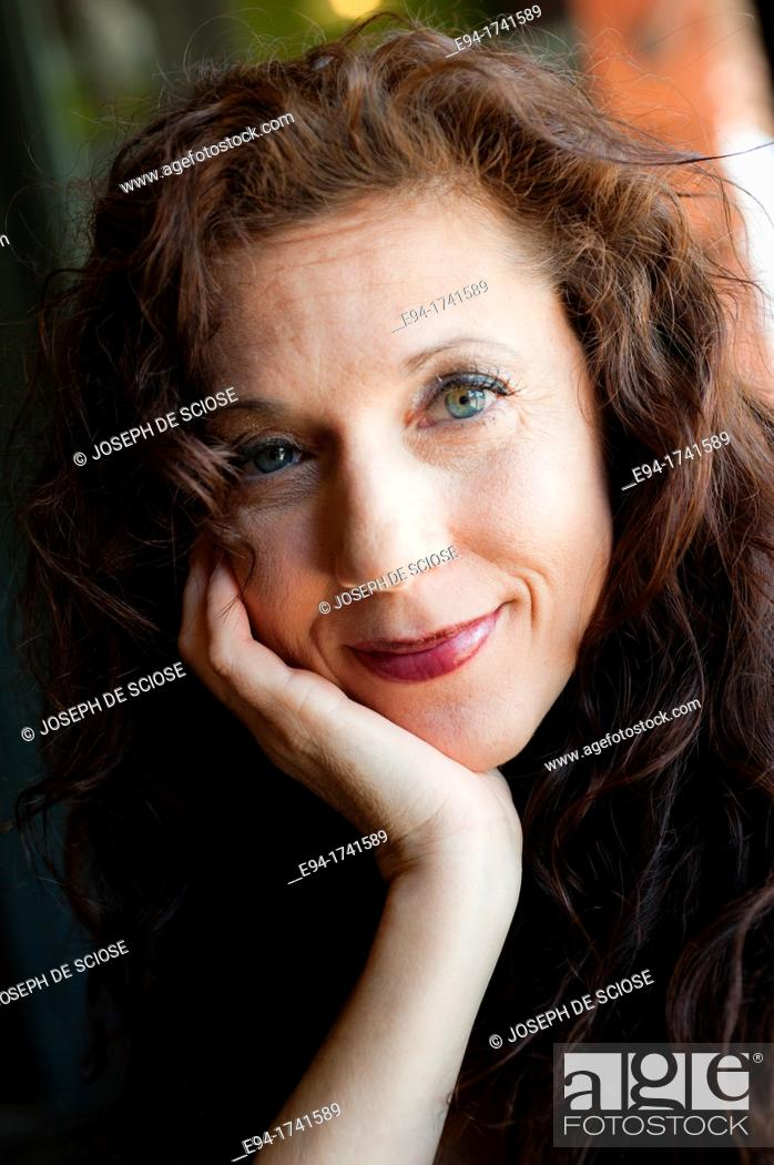 Stock Photo: Portrait of a 42 year old woman with long curly black hair smiling at the camera, chin resting in her hand.