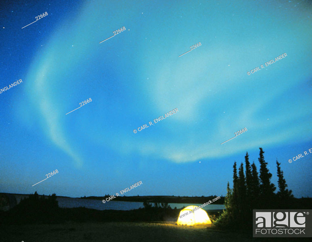 Stock Photo: Northern Lights (aurora borealis) with lighted tent, Northwest Territories, Canada.