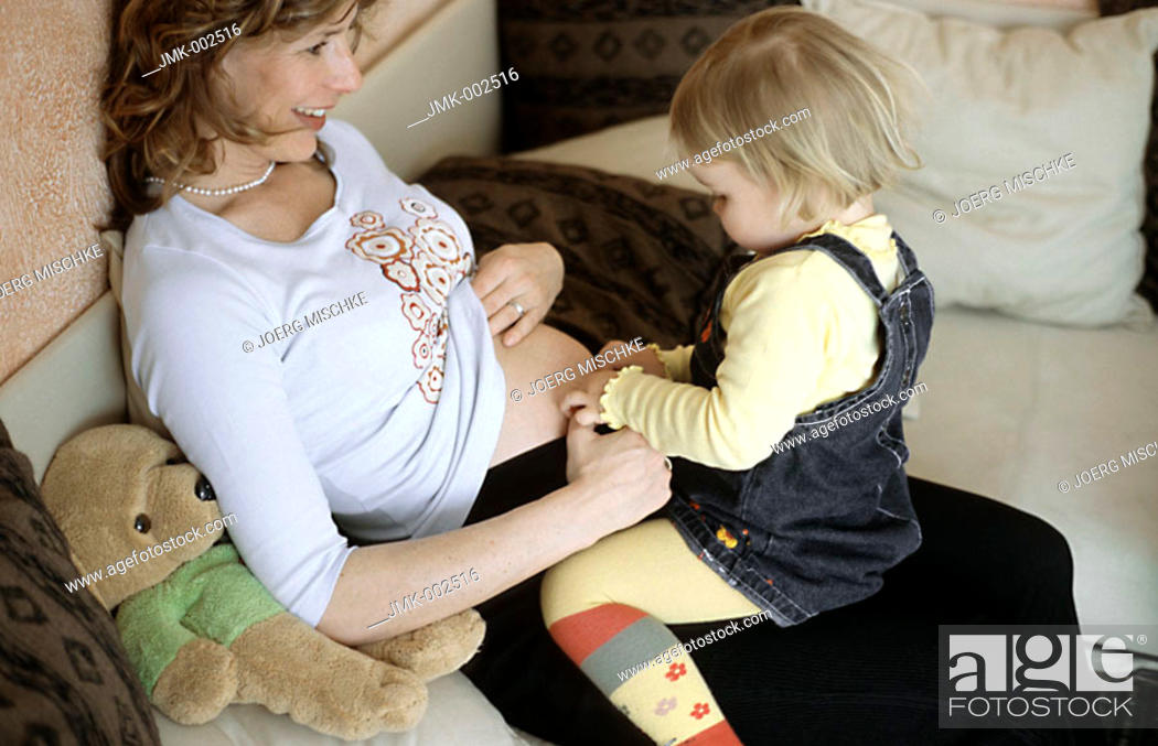 Stock Photo: A young pregnant woman, 25-30 30-35 35-40 years old, sitting on the sofa with her little daughter, 1-5 years old.