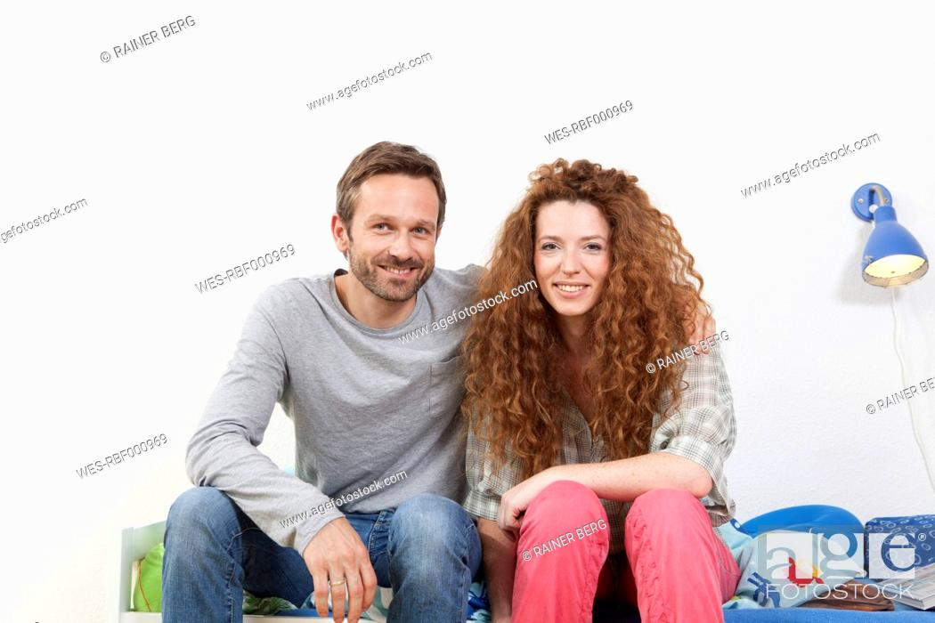 Stock Photo: Germany, Berlin, Couple sitting on bed, smiling, portrait.