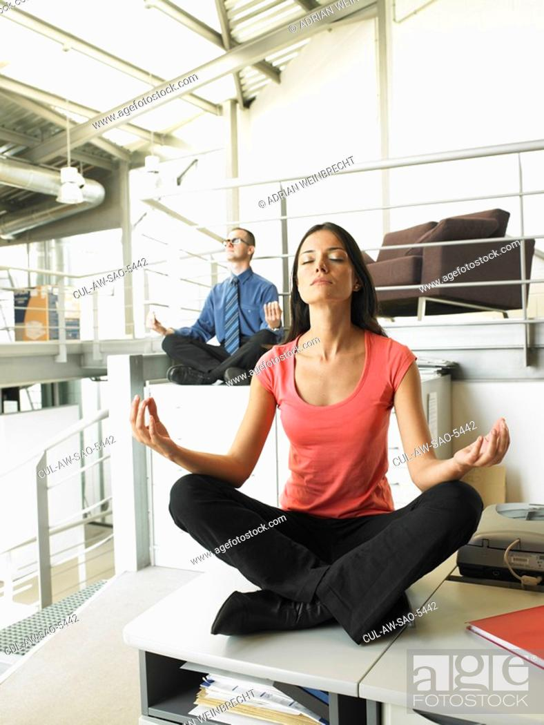 Stock Photo: Young adults sitting on office desks in a yoga position.