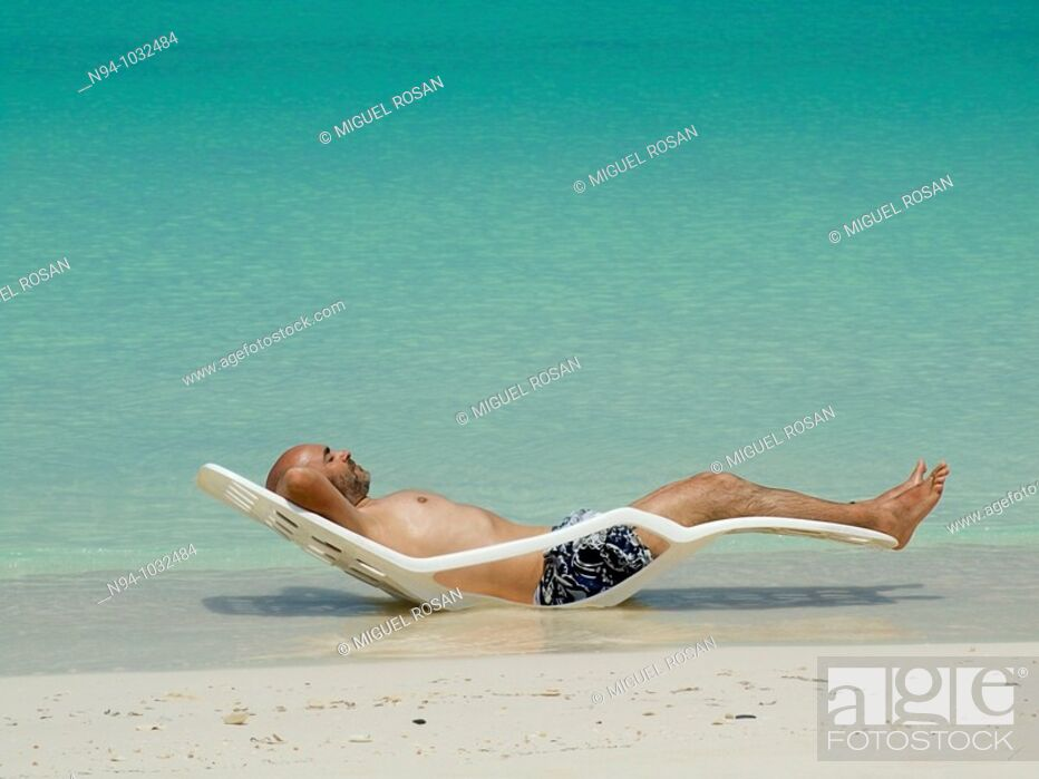 Stock Photo: Young man, bald with a beard, lying in a hammock in the sun on the edge of the Caribbean beach in Cayo Levisa Cuba.