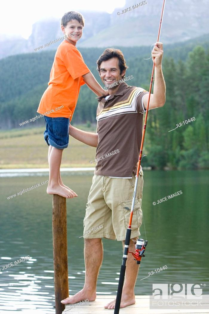 Stock Photo: Father with fishing rod by son 6-8 on pole on jetty, smiling, portrait.