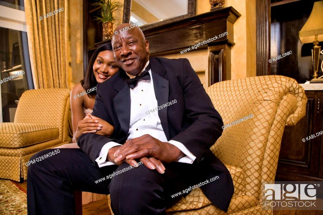 c14ad27a62d Stock Photo - Portrait of teenage girl posing with father grandfather in formal  attire at home
