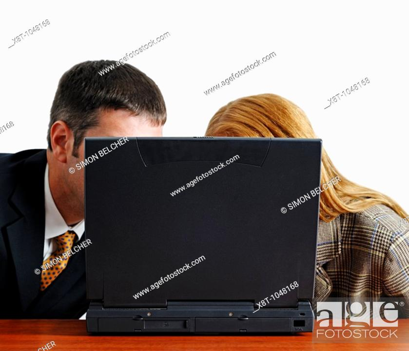 Stock Photo: Businessman and Woman Looking at the Monitor of a Laptop in an Office.