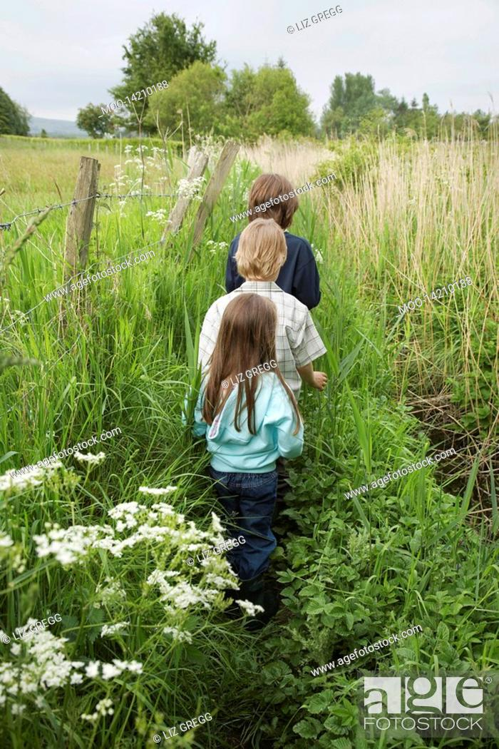 Stock Photo: Three children 5-9 walking in countryside.