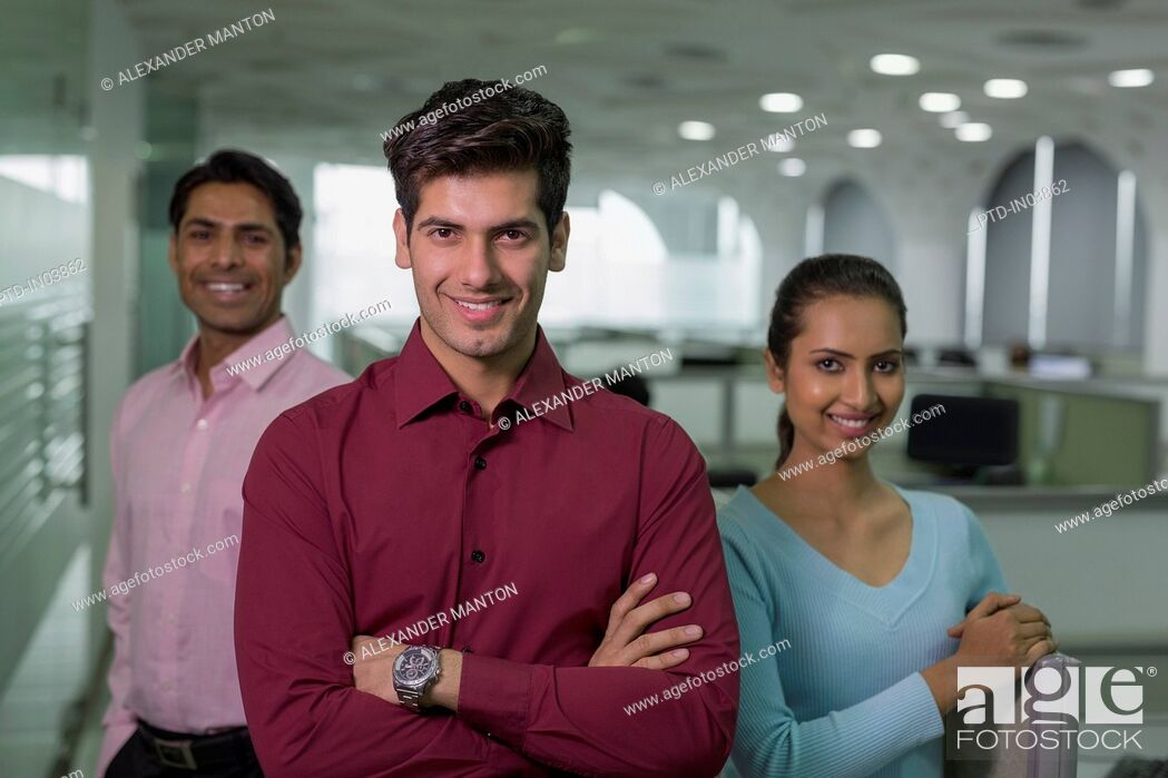 Stock Photo: India, Smiling businessman in front of colleagues in office.