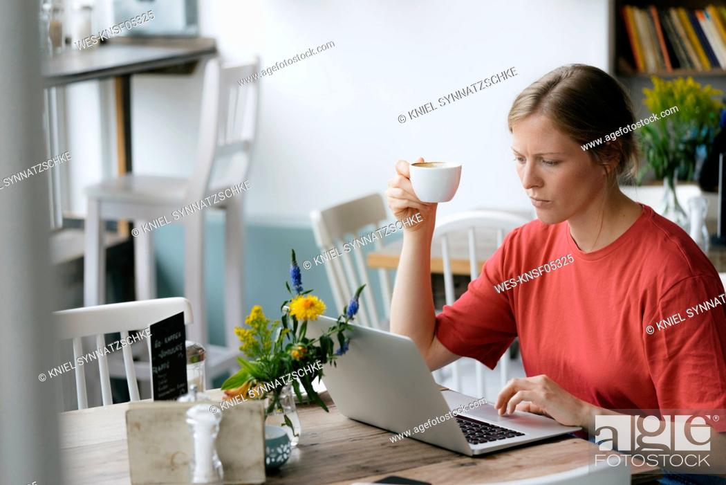 Stock Photo: Young woman using laptop at table in a cafe.
