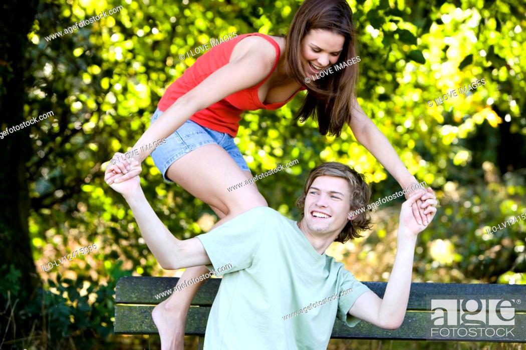 Stock Photo: A young couple having fun on a park bench.
