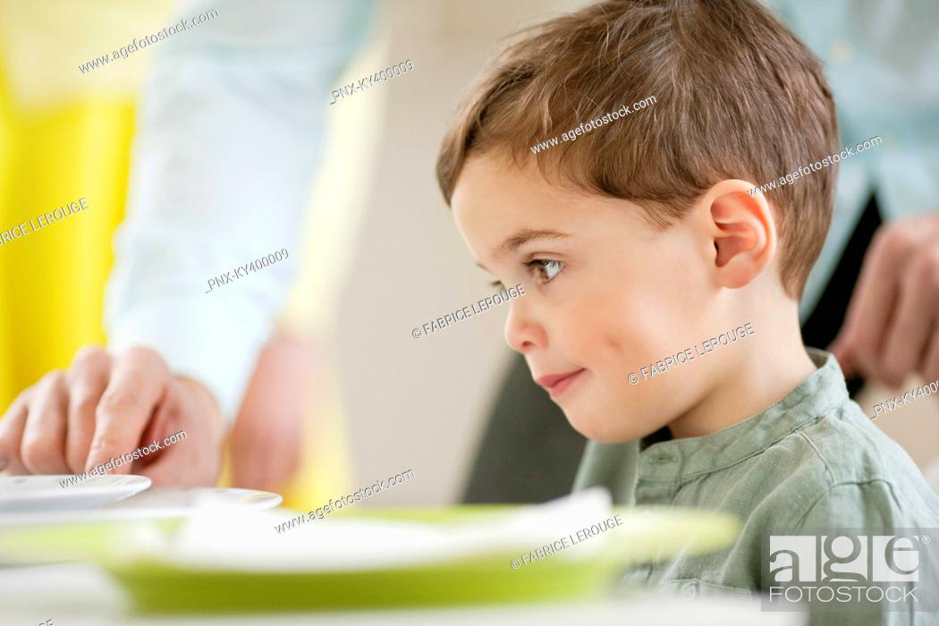 Stock Photo: Boy sitting at a dining table.
