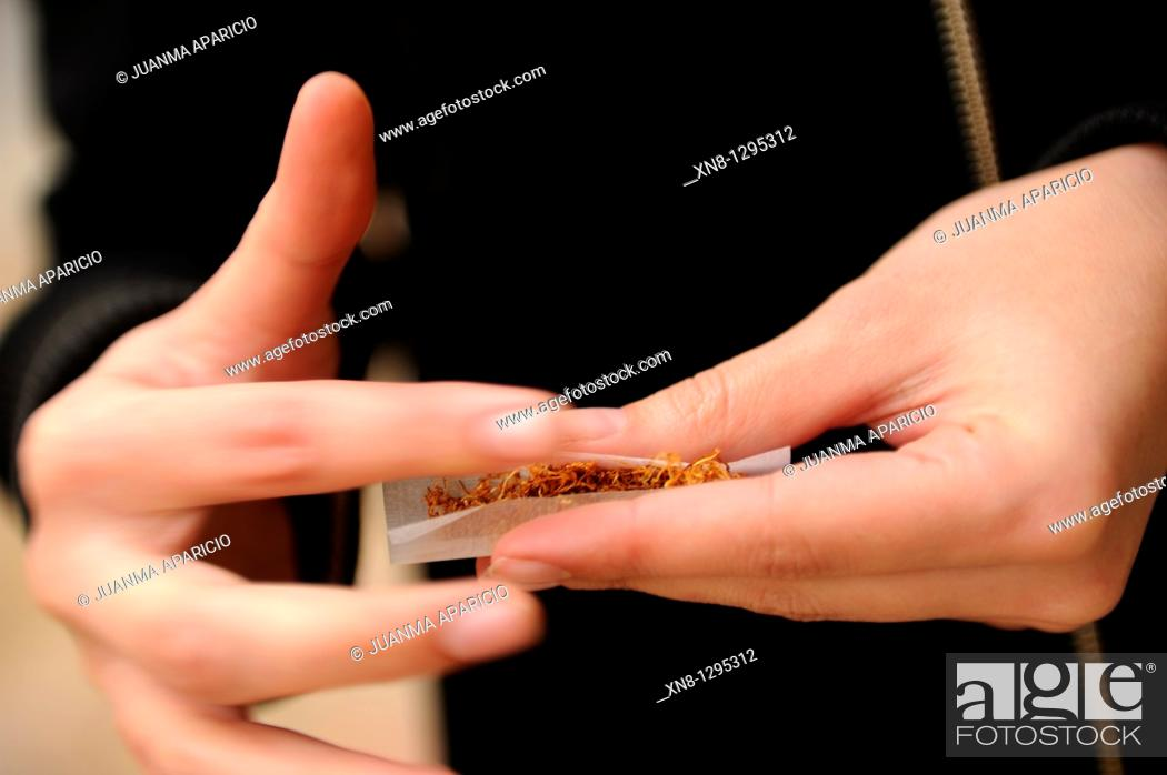Stock Photo: Young woman rolling a joint.