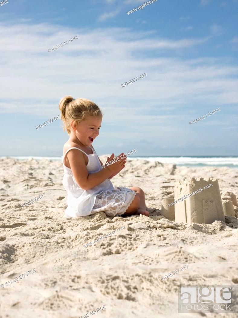 Stock Photo: Happy girl with sandcastle.