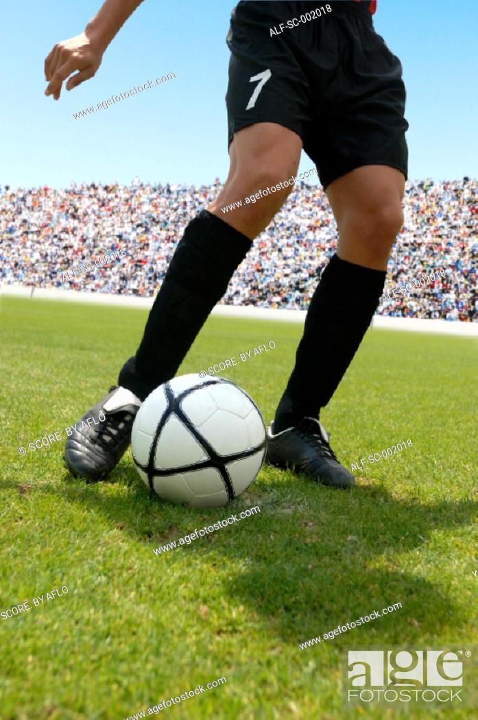 Stock Photo: Soccer player striking ball.