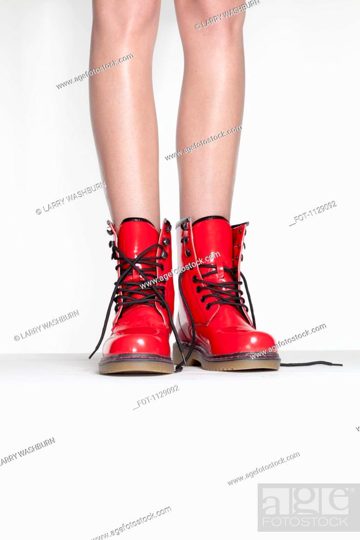 Stock Photo: A woman wearing red patent leather boots, low section.