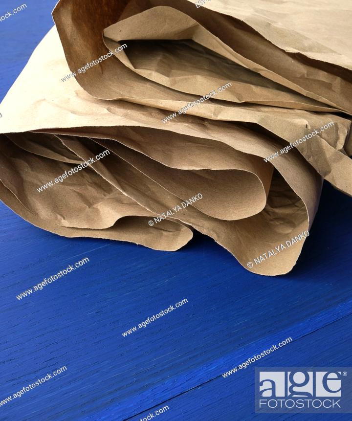 Stock Photo: folded brown crumpled kraft paper sheet on blue wooden background, close up.