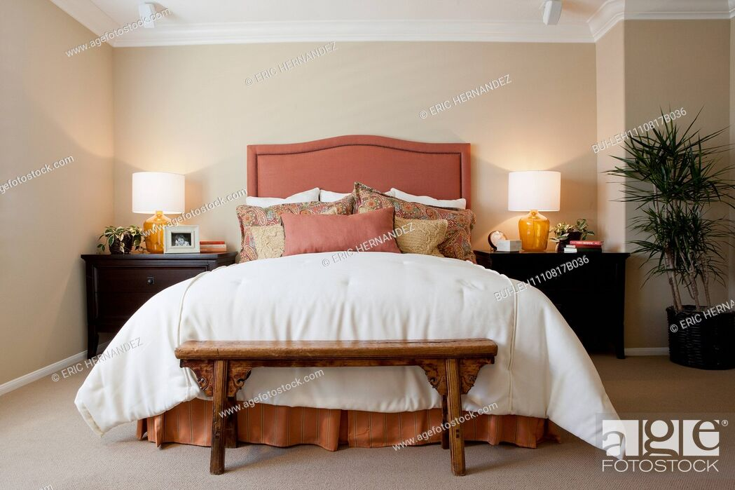 Stock Photo: Arranged pillows on tidy bed with lit table lamps in the bedroom at home; California; USA.