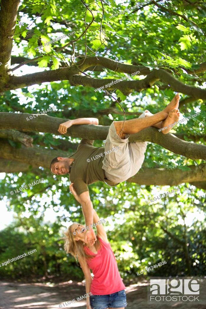 Stock Photo: A young man hanging from a tree, girlfriend tickling him.