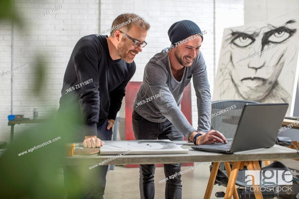 Stock Photo: Smiling artist using laptop with man in studio.