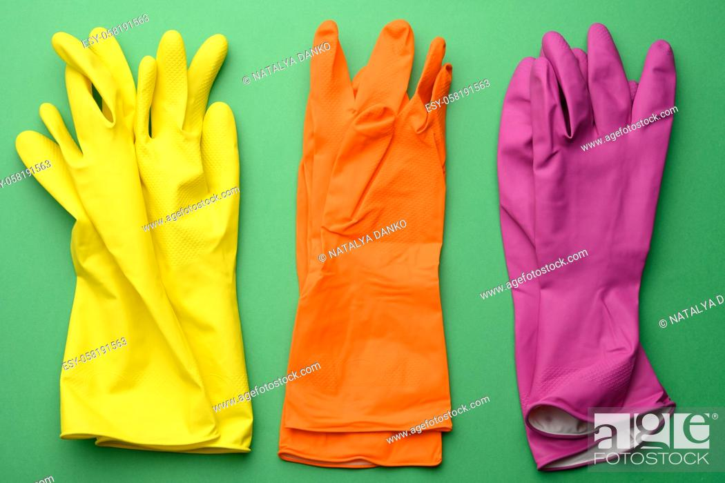 Stock Photo: three pairs of rubber gloves for cleaning on a green background, top view.
