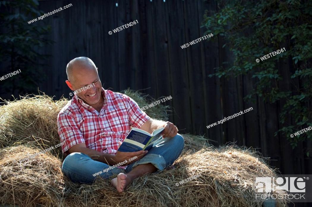 Stock Photo: Germany, Bavaria, Senior man sitting on haystack, reading a book.