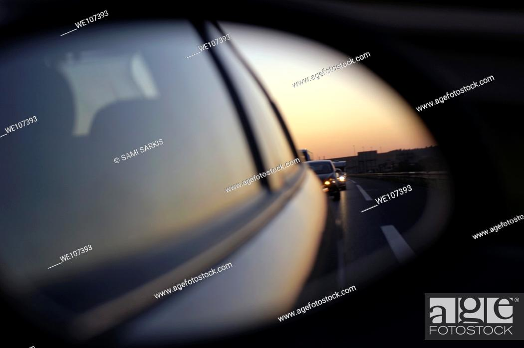Stock Photo: Left side rear view mirror reflecting traffic on the highway.