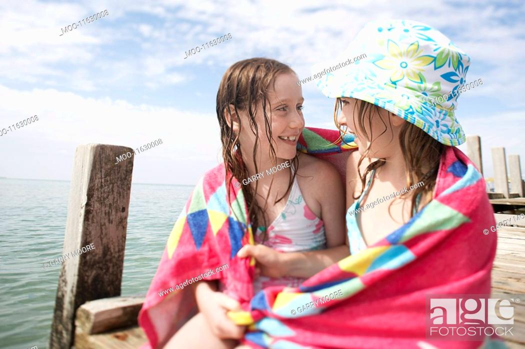 Stock Photo: Two girls wrapped in towel sitting together at end of pier.