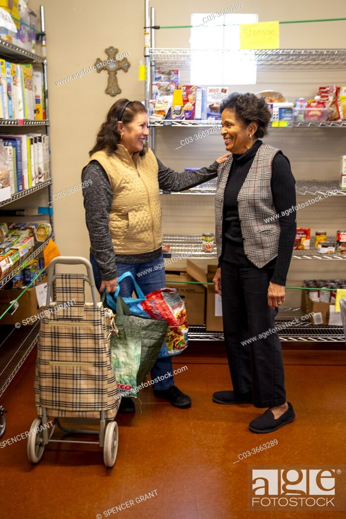 Stock Photo: A Hispanic client at the charity food pantry of a Southern California Catholic church greets an African American church volunteer. Note cross on wall.