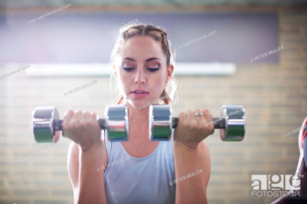 Stock Photo: Trainer watching female client lifting dumbbells in gym.