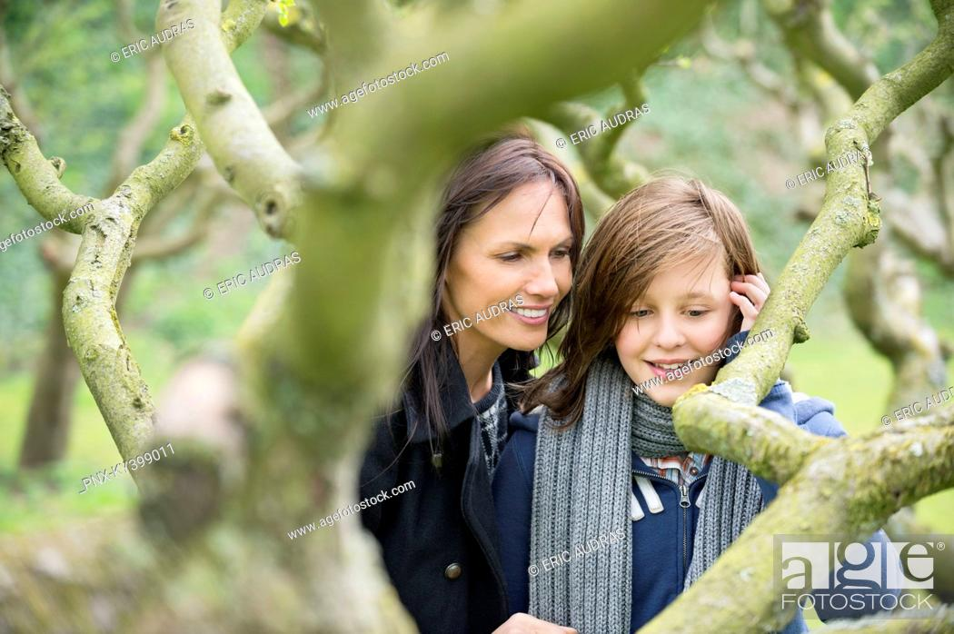 Stock Photo: Woman with her daughter looking at a tree branch in an orchard.