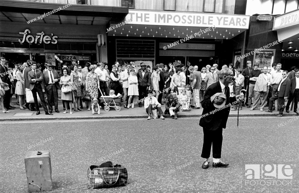 Stock Photo: A street entertainer performs a trick involving a tartan bag and a wooden box, much to the amusement of the tourists in Leicester Square, London.