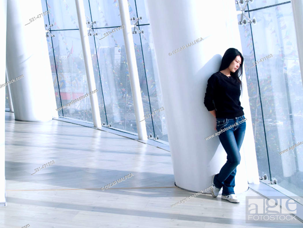 Stock Photo: Chinese woman leaning on a column in a shopping mall.