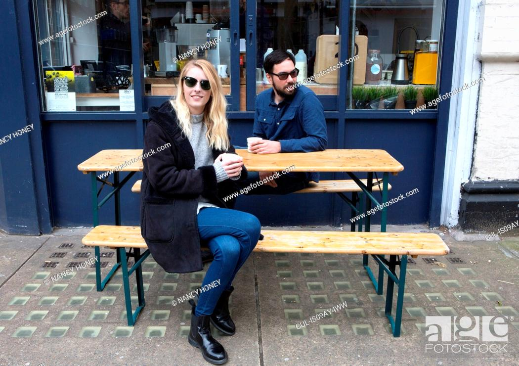 Stock Photo: Couple sitting watching from sidewalk cafe table.