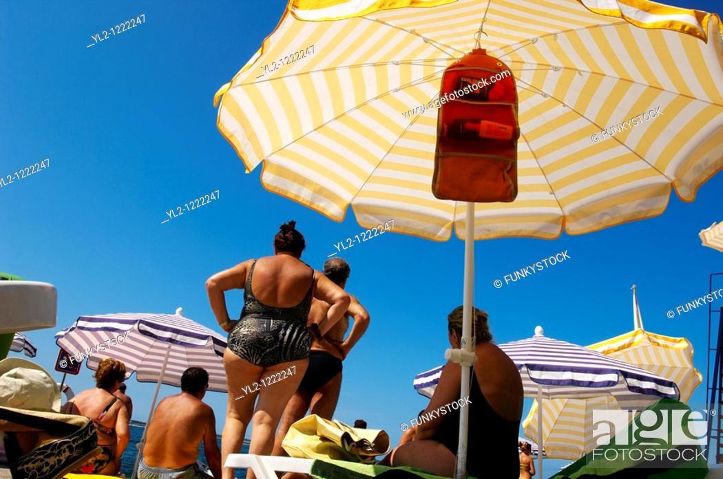 Stock Photo: Sunbathers sitting on sun beads looking at the sea  Piran , Slovenia.