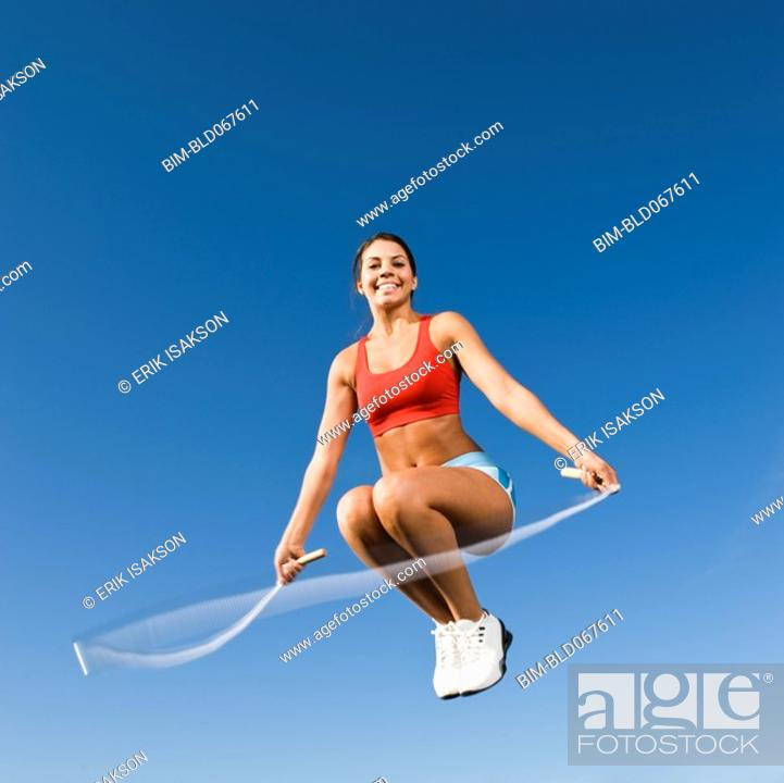 Stock Photo: Native American woman jumping rope in mid-air.