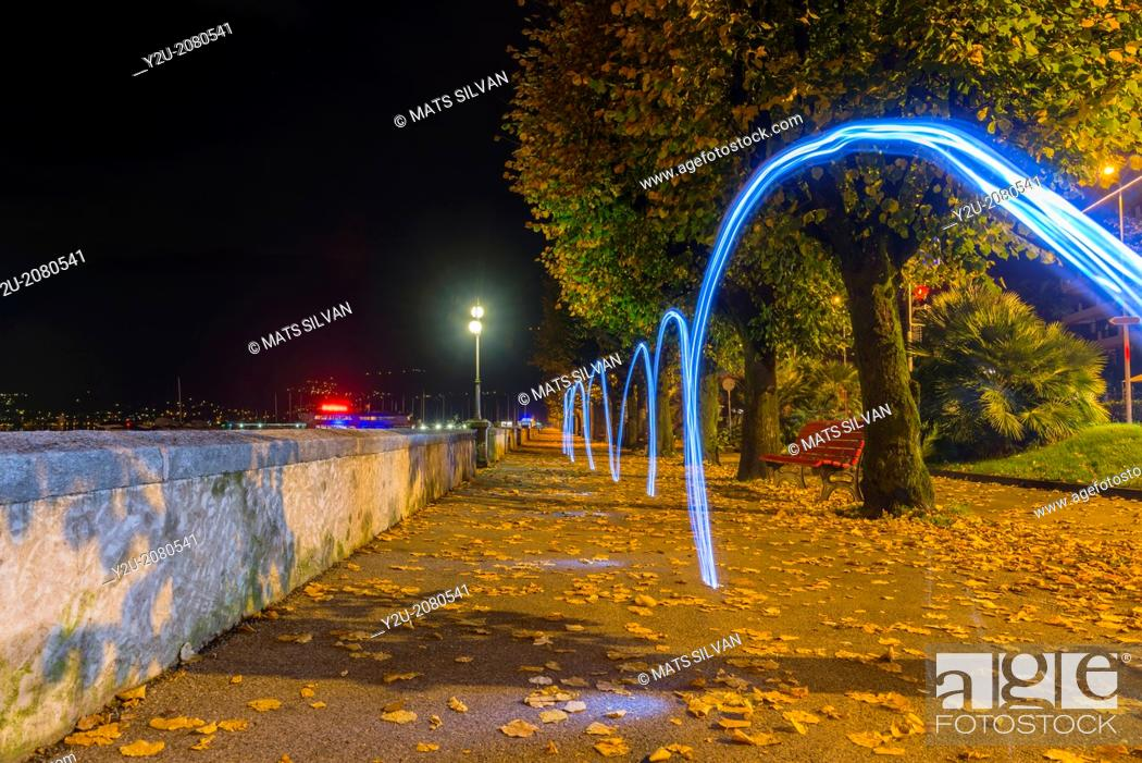 Stock Photo: Light trails on the walkway in autumn at night in locarno ticino switzerland.