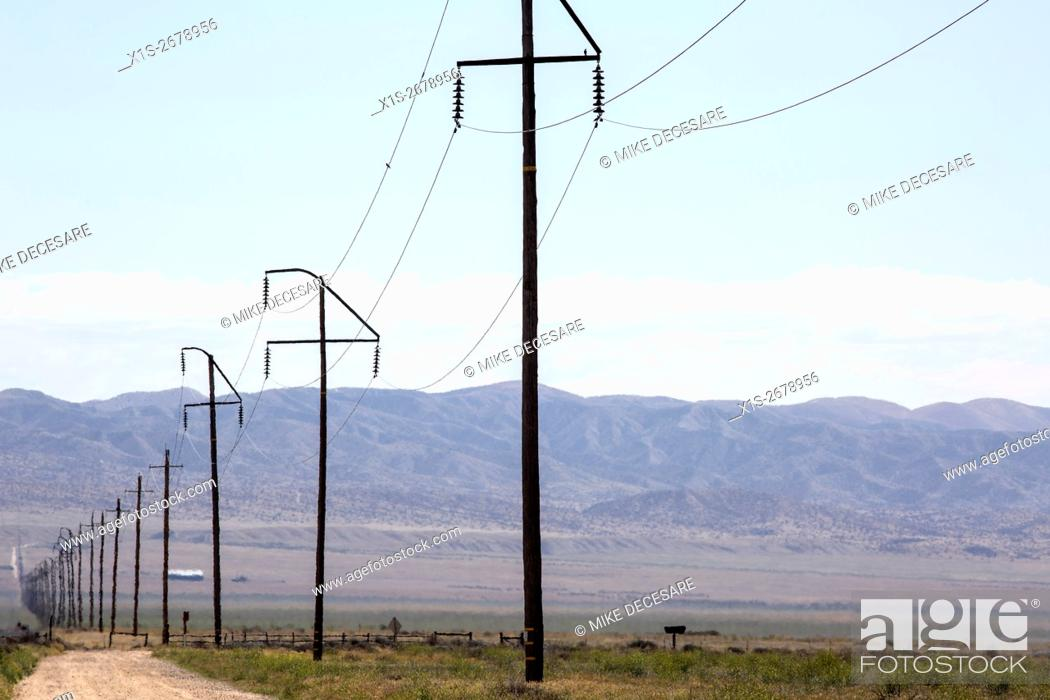 A straight line of power poles and power lines disappears into the