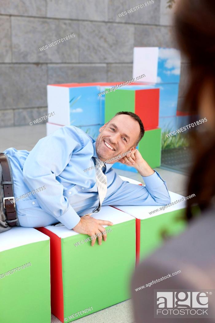 Stock Photo: Germany, Leipzig, Business people resting on cubes.
