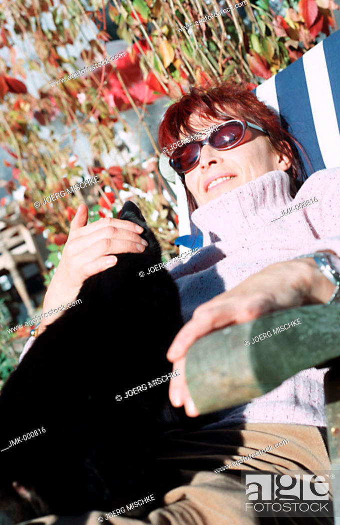 Stock Photo: Woman outside in the autumnal garden, sitting in a deckchair with a cat on her lap.