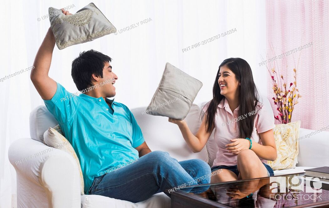 Stock Photo: Brother and sister fighting with pillows.