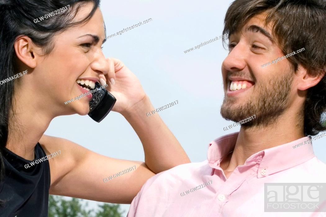 Stock Photo: Young woman talking on a mobile phone with a young man smiling.